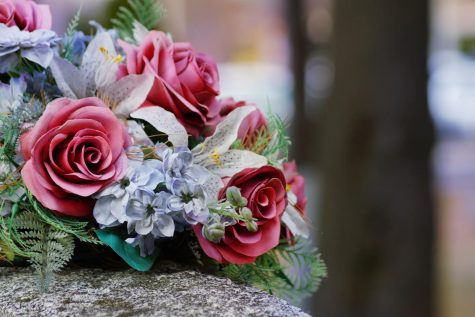 a bouquet of flowers resting on top of a tombstone